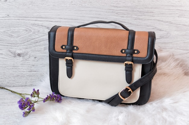 Women's white and brown bag on white fur. fashionable