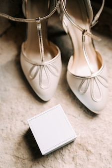 Women's white shoes and a box for rings on a stone texture.