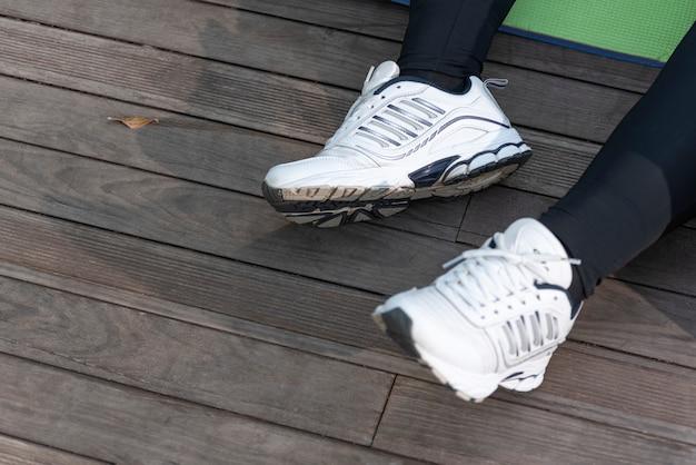 脚に女性用の白いスニーカー。ランニングシューズ。スポーツシューズ。ジョギング後に休んでいる女性