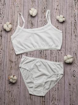 목화 꽃이 핌이있는 나무 표면에 여성용 흰색 속옷. 흰색 속옷. 평평하다.
