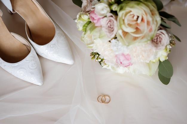 花束と結婚指輪の女性の白いウェディングシューズ