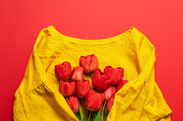 Women's yellow cotton blouse and a bouquet of tulips, top view