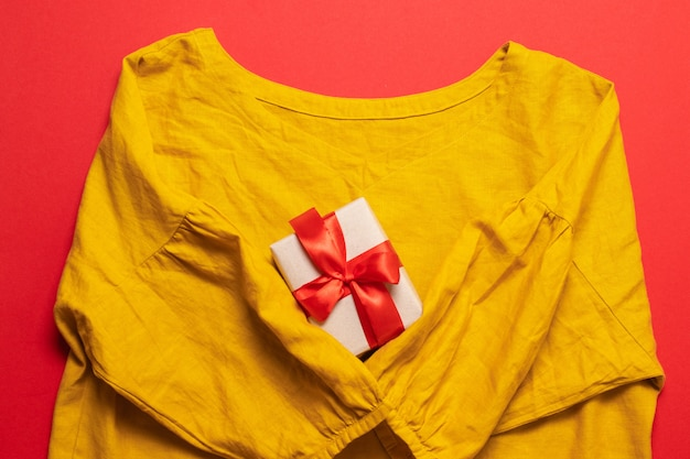 Women's yellow cotton blouse and and gift box on red background.