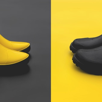 Women's yellow rubber boots on a black background and men's black rubber boots on a yellow background stand opposite each other.