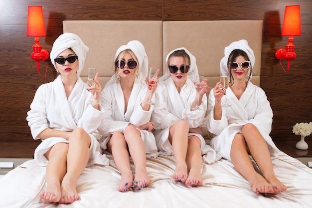 女性の自信。手にシャンパン。サングラス、バスローブ、タオルターバン。ホテルの部屋。