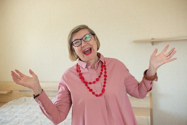 Women senior doing funky action gray hair woman, middle aged smile old woman wearing glasses at home, positive lonely senior pensioner woman happiness