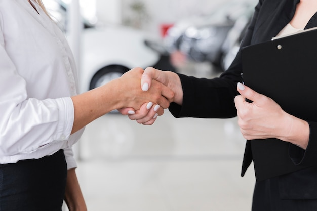 Women shaking hands in car show room