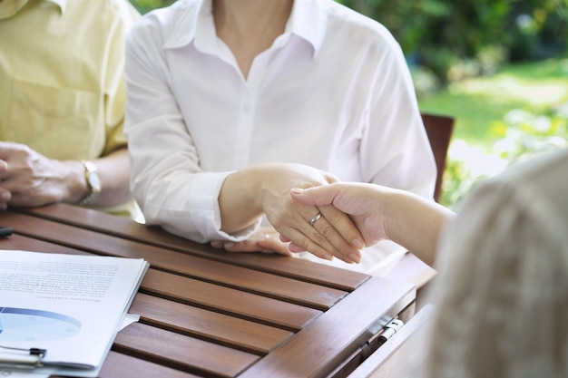 Women shaking hands represent sale, asian couple meeting consulting with insurance agent present analysis data the charts and graphs, individual income tax return, finance business report.