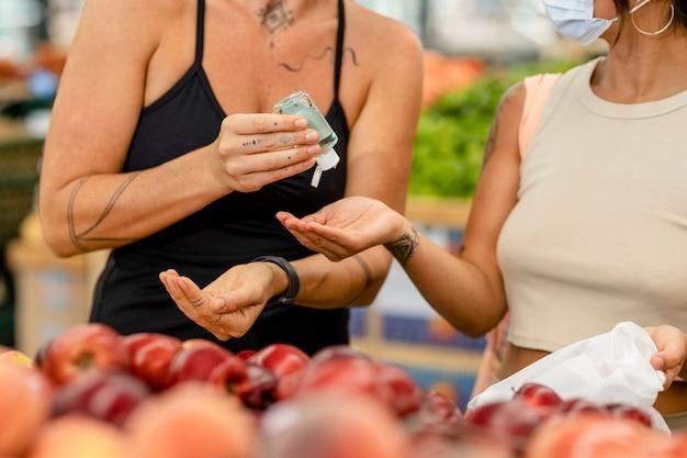 手指消毒剤、食料品の買い物の画像を共有する女性