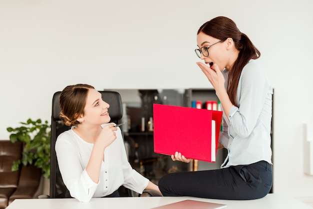 Women sharing news in the office at the workplace