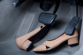 Women shoes placed under car brake and accelerator pedals.