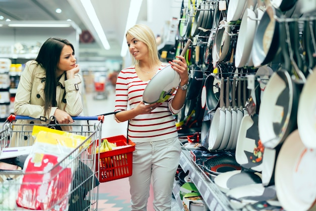 Женщины, покупающие посуду в супермаркете
