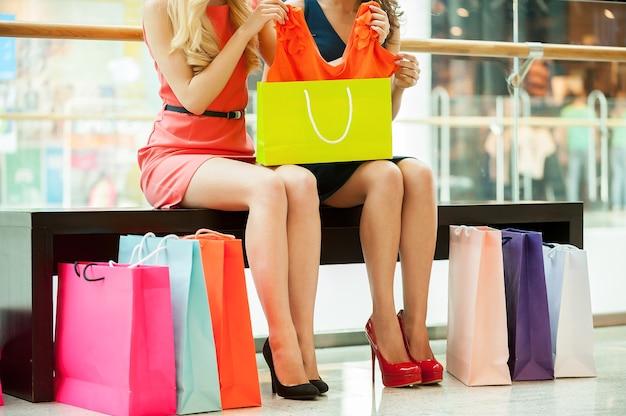 Женщины за покупками. обрезанное изображение двух молодых женщин, сидящих в торговом центре с сумками