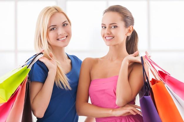 女性の買い物。互いに近くに立って買い物袋を持っているドレスを着た2人の美しい若い女性
