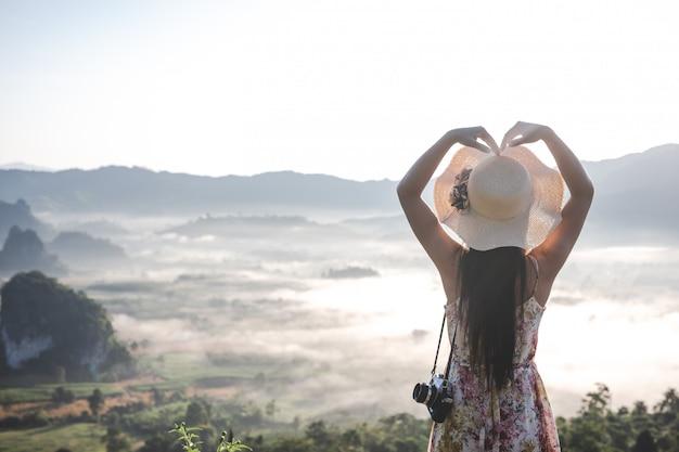 Женщины показывают жесты в форме сердца на смотровой площадке на горе.