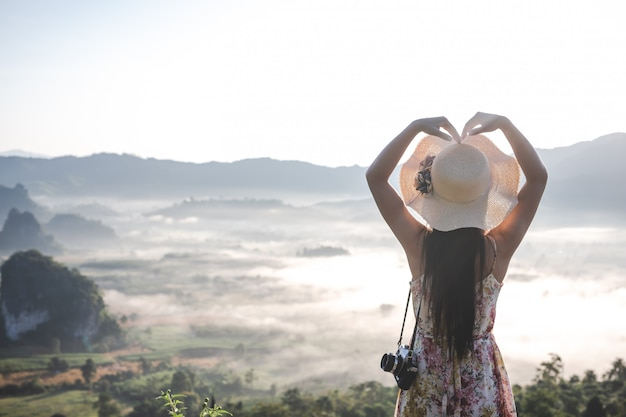 Women show heart-shaped gestures at the viewpoint on the mountain.