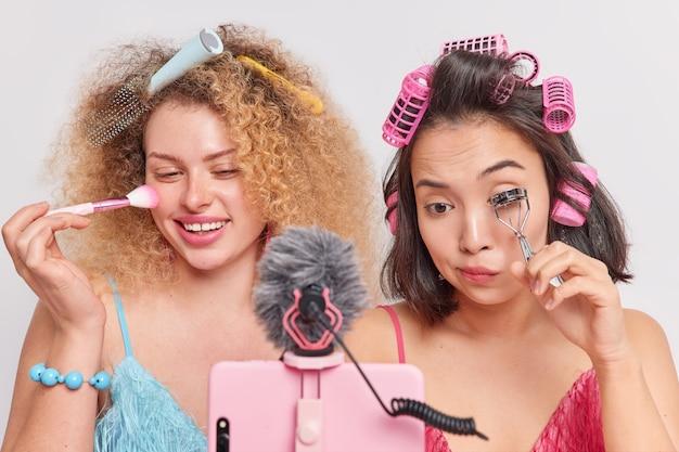 여성들은 스마트폰 웹캠 앞에서 전문 메이크업을 하는 방법을 보여줍니다. 브러시로 얼굴 가루를 바르고 curlers와 함께 속눈썹을 붙입니다. 헤어스타일 녹화 비디오 블로그 추종자들과 이야기