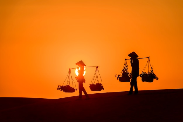 Women silhouette on sand dune at sunset carrying baskets