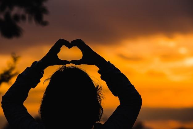 夕暮れの背景にハートの形の手で女性のシルエット