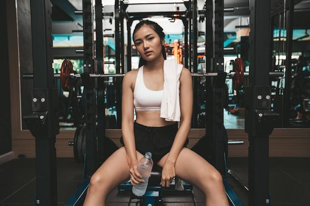 女性は運動後に座ってリラックスします。水のボトルを持ち、首に白い布を持っています。