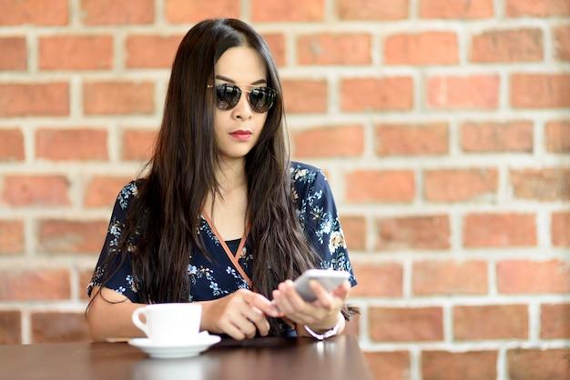 女性はコーヒーショップの木製テーブルに座って待っています。