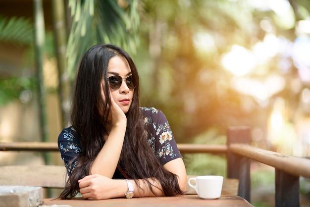 女性は座って庭の木製テーブルで待っています。
