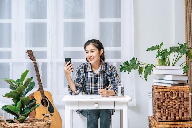 Женщины сидят за столом и координируют свои действия по телефону.