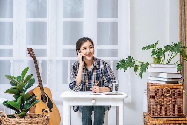 女性は机に座って電話を使って調整します。
