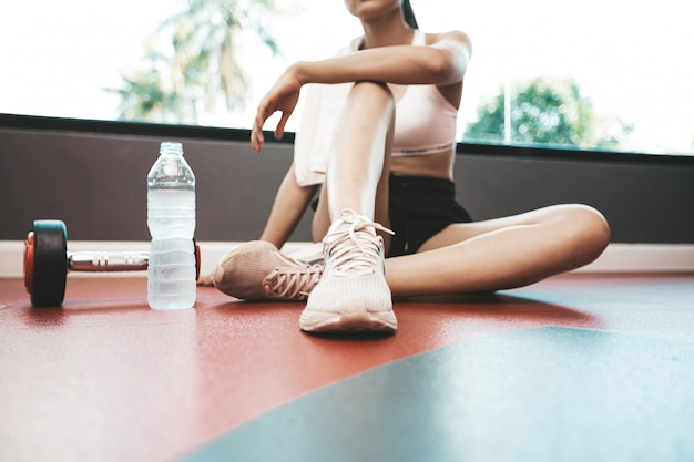 Women sit back and relax after exercise. there is a water bottle and dumbbells.