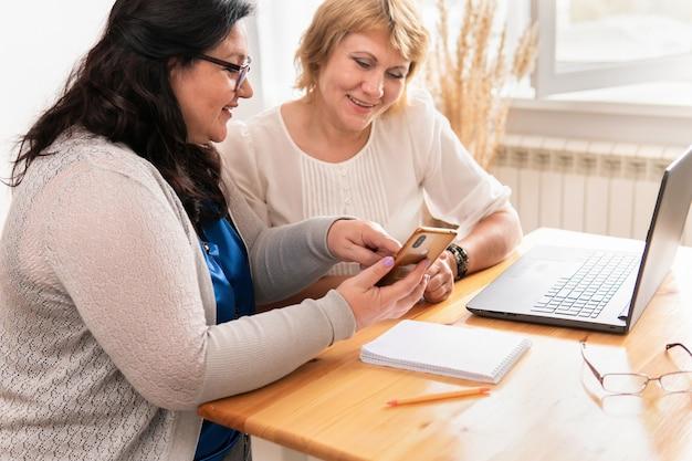 여성들은 노트북 근처 사무실에 앉아 프로젝트에 대해 토론합니다.