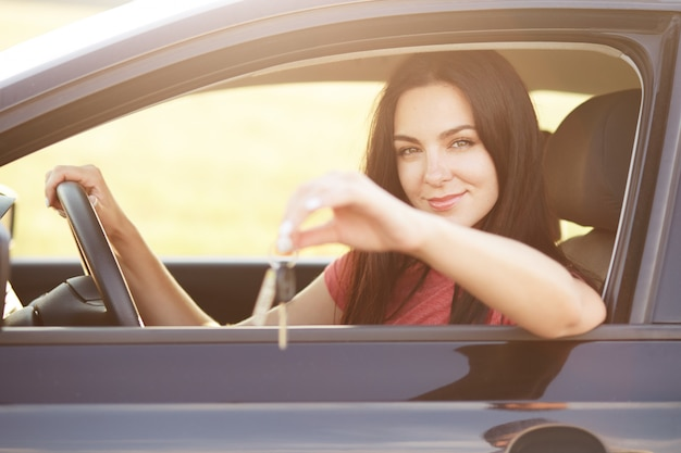 Women sits at drivers seat, keeps hand on wheel, advertises or sells car. beautiful brunette woman drives vehicle