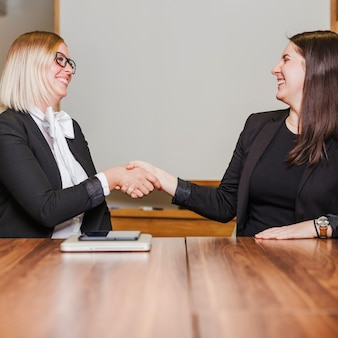 Женщины, сидя на столе, рукопожатие улыбается