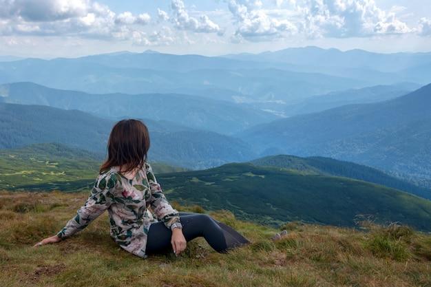 山の頂上に座っている女性が谷と山を眺めています。