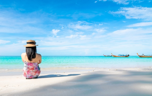 Women sitting back on the beach and sea have a holiday summer relaxing