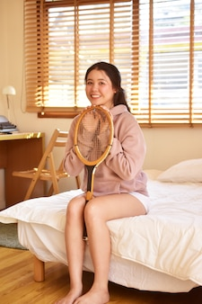 Women sitting on the bed in the bedroom and holding a tennis racket,women sitting in room