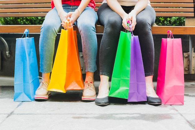 Women sitting on bench with shopping bags