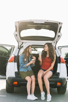 Women sitting on car trunk with food