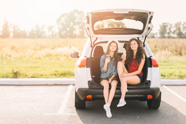 Women sitting on car trunk with ice cream