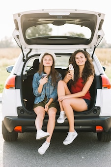 Women sitting on car with ice cream