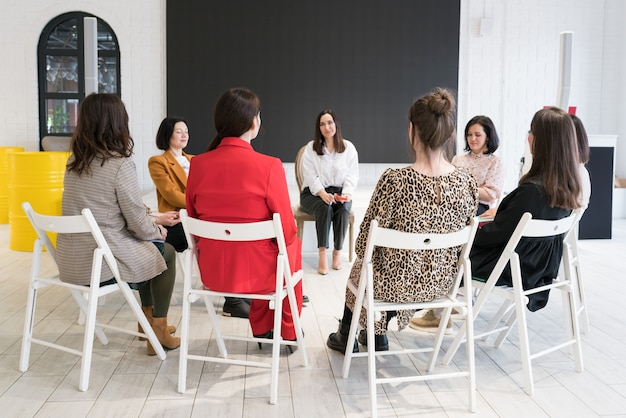 Women sitting on chairs in circle and talking to  psychologist