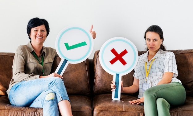 Women sitting on couch holding tick icons