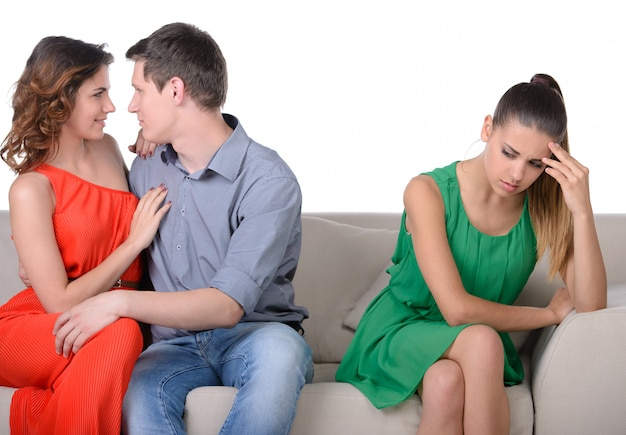 Women sitting on couch while another women with man.