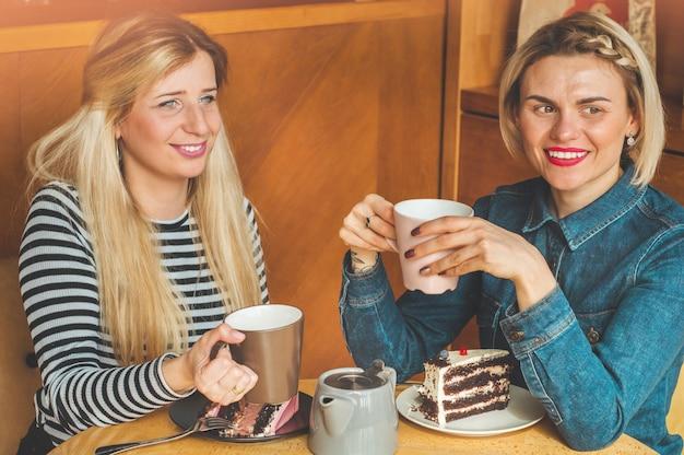 カフェに座って熱いお茶を飲む女性