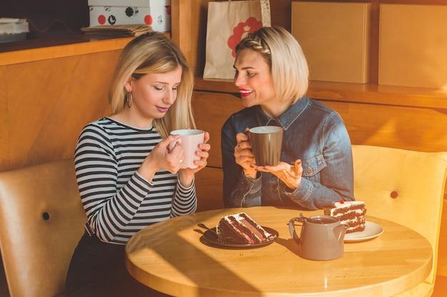 Женщины сидят в кафе и пьют горячий чай