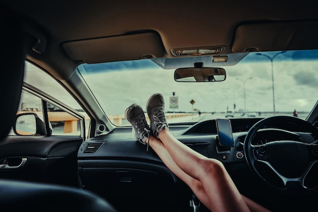 자동차 대시보드에 발을 놓고 차에 앉아 있는 여성. car.on 여름 여행 휴가에서 편안한 젊은 여자. 여행 개념입니다.