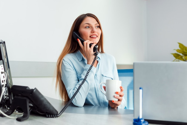 Women sitting in the office talking on the phone and holding a cup