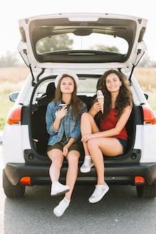 Women sitting on car with ice cream