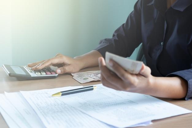 電卓を使用してお金を入れる机の上に座っている女性