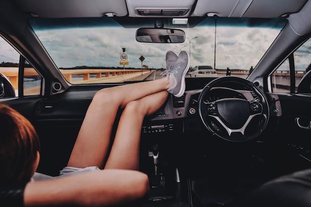 자동차 대시보드에 발이 있는 차의 조수석에 앉아 있는 여성. 차에서 편안한 젊은 여자. 여름 여행 휴가에. 여행 개념입니다.