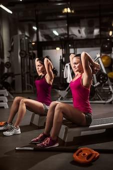 스테퍼에 앉아 아령 운동을하는 여성. 체육관 iinterior.